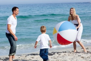 Familie am Strand mit Wasserball